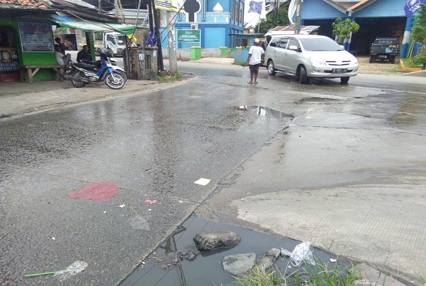 Pertigaan Jalan Raya Papan Mas arah Flyover Pasar Tambun, Kabupaten Bekasi kondisinya tergenang air selokan yang mampet.
