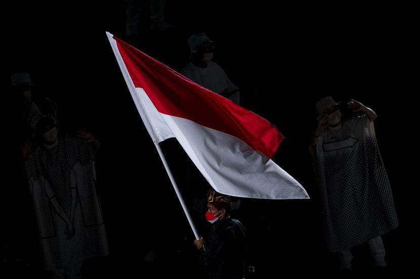 Peselancar Indonesia Rio Waida membawa bendera Merah-Putih saat defile pembukaan Olimpiade Tokyo 2020 di Stadion Nasional, Tokyo, Jepang, Jumat (23/7/2021)