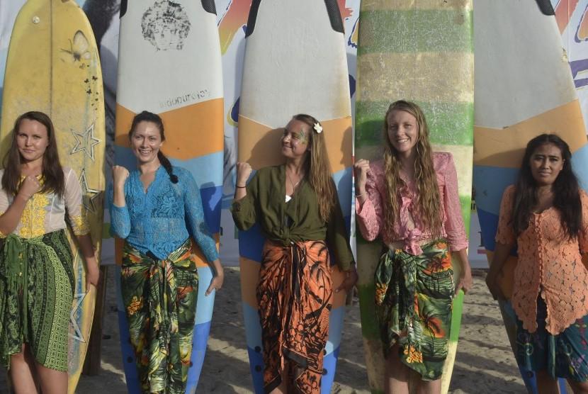 Peselancar wanita yang mengenakan kebaya berfoto sebelum berselancar untuk memeriahkan peringatan Hari Kartini di Pantai Kuta, Bali, Sabtu (20/4/2019). Kegiatan tersebut digelar untuk membangkitkan semangat perjuangan Kartini serta mengenalkan kebaya kepada wisatawan mancanegara.