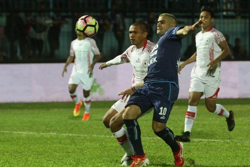 Pesepak bola Arema FC Cristian Gonzales (kanan) berebut bola dengan pesepak bola Persipura Jayapura Ricardo Salampesy (kiri) dalam pertandingan Liga 1 di Stadion Kanjuruhan, Malang, Jawa Timur, Ahad (16/7). Arema kalah dari Persipura dengan skor akhir 0-2.
