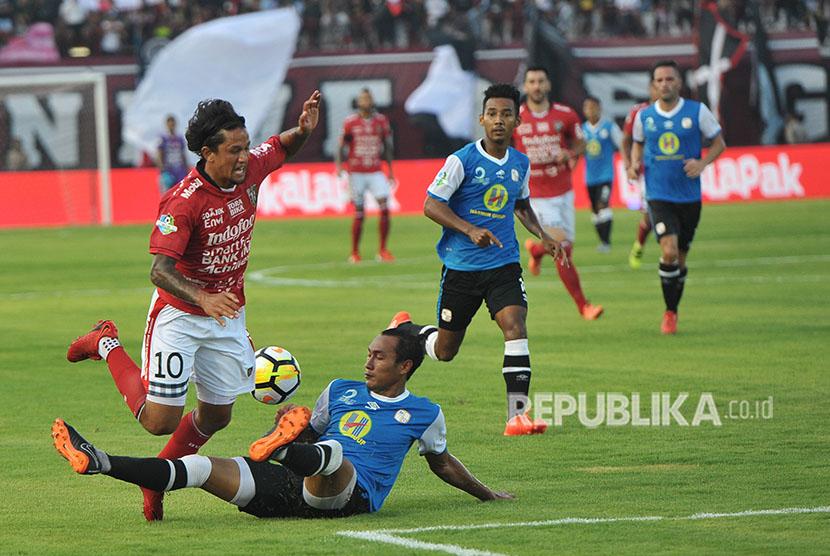 Pesepak bola Bali United Irfan Bachdim (kiri) berebut bola dengan pesepak bola Barito Putra Hansamu Yama Pranata (bawah) dalam Pertandingan Sepak Bola Liga 1 2018 di Stadion I Wayan Dipta, Gianyar, Bali, Minggu (22/4).