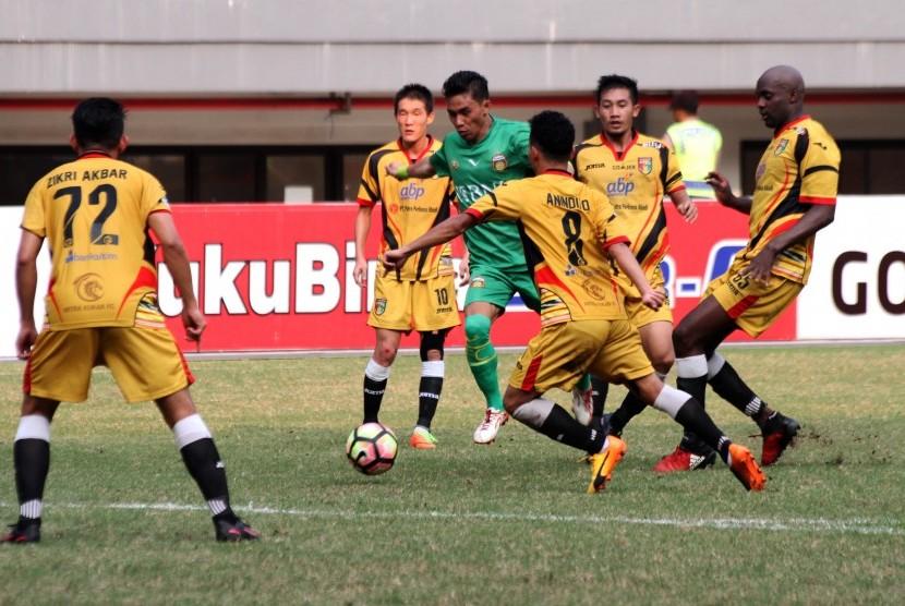 Pesepak bola Bhayangkara FC Alsan Putra Masat Sanda (tengah) menggiring bola melewati hadangan pesepak bola Mitra Kukar pada pertandingan Liga 1, di Stadion Patriot Candrabhaga, Bekasi, Jawa Barat, Jumat (21/7).
