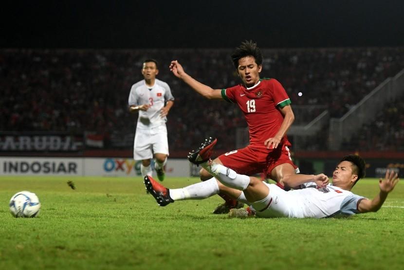 Pesepak bola Indonesia U-19 Hanis Saghara Putra (kiri) berebut bola dengan pesepak bola Vietnam U-19 dalam laga penyisihan grup A Piala AFF U19 Dang Van Toi (kanan) di Gelora Delta Sidoarjo, Sidoarjo, Jawa Timur, Sabtu (7/7).