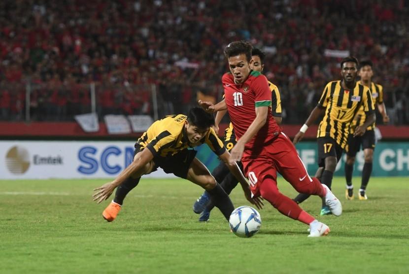 Pesepak bola Indonesia U19 Egy Maulana Vikri (kanan) menggiring bola yang dihalangi pesepak bola Malaysia U19 Muhammad Anwar (kiri) pada semi final Piala AFF U19 di Gelora Delta Sidoarjo, Sidoarjo, Jawa Timur, Kamis (12/7).