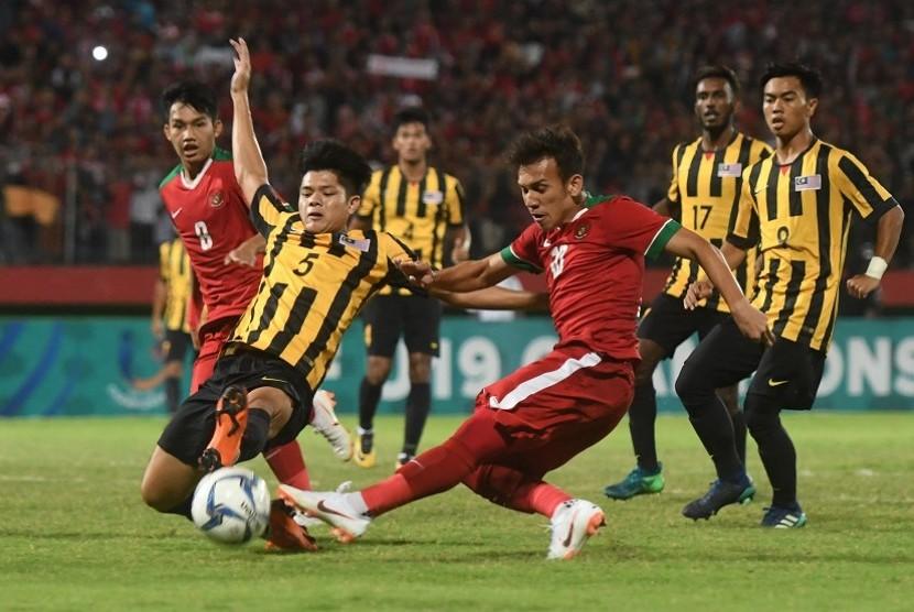 Pesepak bola Indonesia U19 Egy Maulana Vikri (tengah) menendang bola yang dihalangi pesepak bola Malaysia U19 Muhammad Anwar (kiri) pada semi final Piala AFF U19 di Gelora Delta Sidoarjo, Sidoarjo, Jawa Timur, Kamis (12/7).