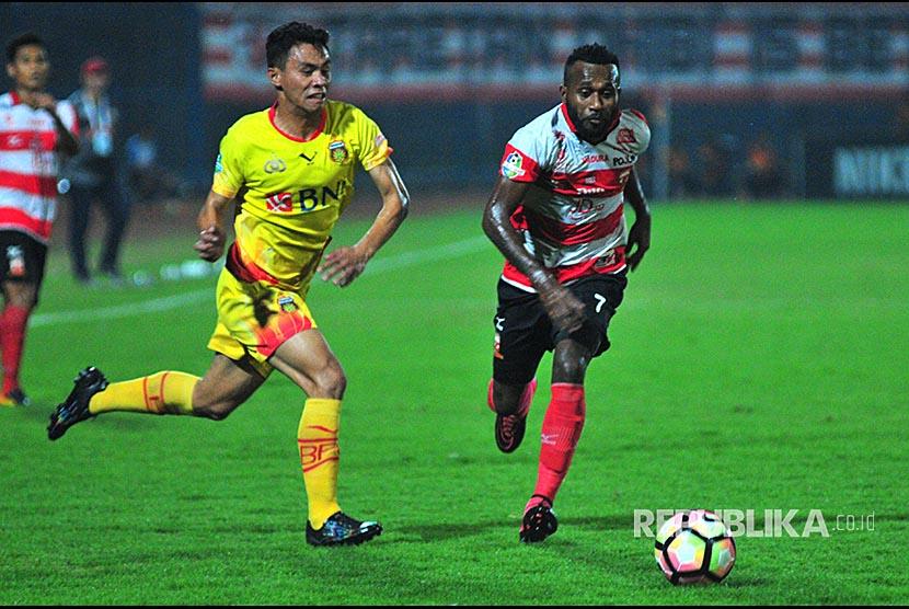 Pesepak bola Madura United FC (MUFC) Engelberd sani (kanan) berebut bola dengan  pesepak bola Bhayangkara FC,  Aslan Sanda (kiri) dalam laga Gojek Traveloka Liga 1 di Stadion Gelora Bangkalan (SGB) Bangkalan, Jawa Timur, Rabu (8/11).