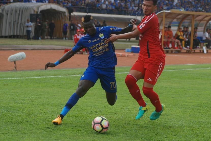 Pesepak bola Persib Bandung Ezechiel Ndouasel (kiri) berebut bola dengan pesepak bola Semen Padang FC Agung Prasetyo (kanan) pada laga lanjutan Liga 1 di Stadion Si Jalak Harupat Soreang, Kabupaten Bandung, Jawa Barat, Sabtu (9/9).