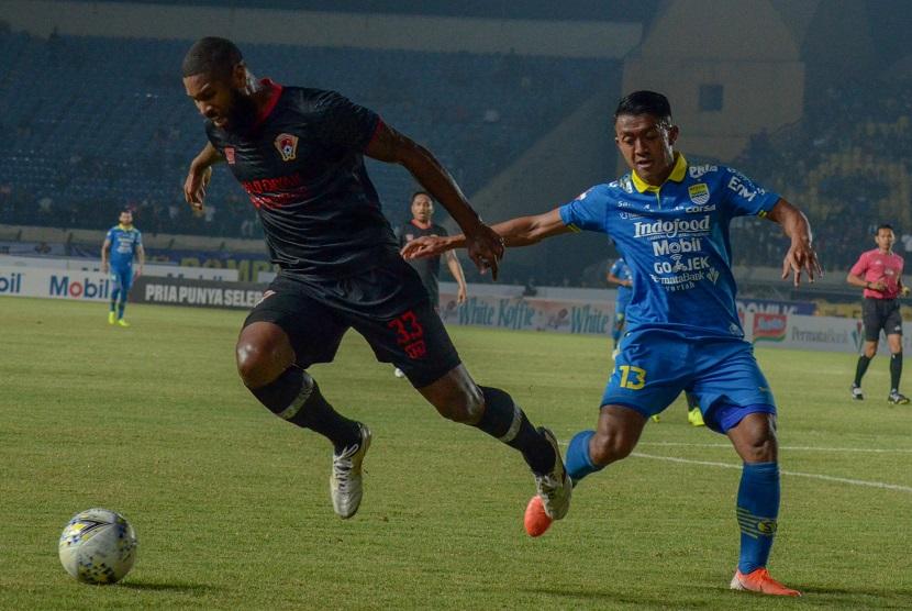 Gelandang Persib Bandung Febri Hariyadi (kanan) berebut bola dengan pemain Kalteng Putra Rafael Bonfim pada pertandingan lanjutan Liga 1 di Stadion Jalak Harupat, Kabupaten Bandung, Jawa Barat, Selasa (16/7).