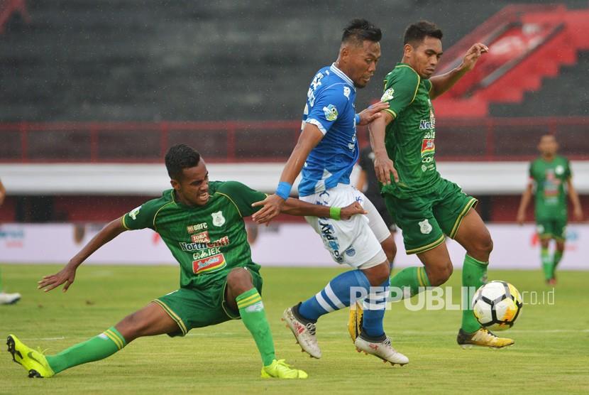 Pesepak bola Persib Bandung, Tony Sucipto (tengah) berebut bola dengan pemain PSMS Medan, Muhammad Alwi Slamat (kiri) dan Frets Butuan (kanan) dalam pertandingan Sepak Bola Liga 1 di Stadion I Wayan Dipta, Gianyar, Bali, Jumat (9/11/2018).