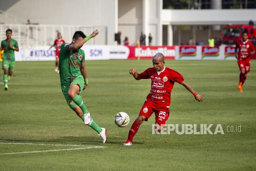 Pesepak bola Persija Riko Simanjuntak (kanan) berebut bola dengan pesepak bola Kalteng Putra Dendi Agustan (kiri) pada laga Shopee Liga 1 di Stadion Madya GBK, Senayan, Jakarta, Selasa (20/8/2019).