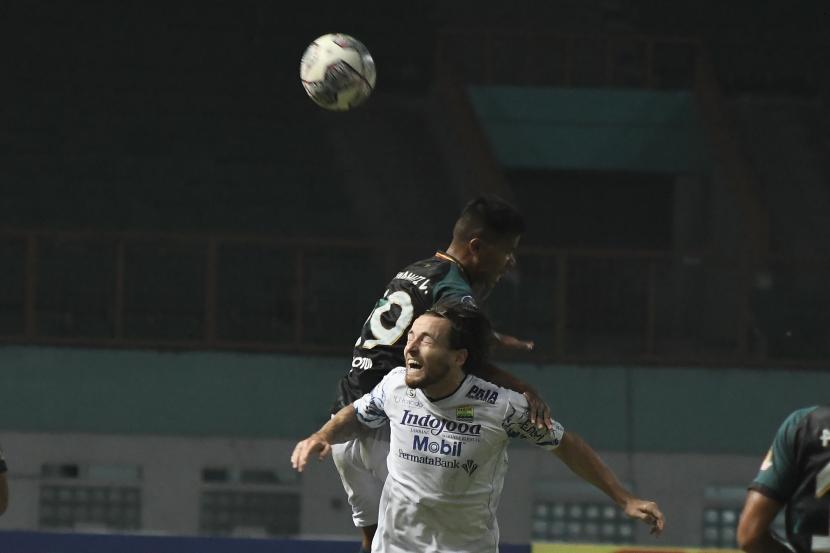 Pesepak bola Persikabo 1973 Manahati Lestusen (kiri) berebut bola dengan gelandang Persib Bandung Marc Klok (kanan) pada lanjutan Liga 1 di Stadion Wibawa Mukti, Kabupaten Bekasi, Jawa Barat, Senin (27/9/2021). Pertandingan babak pertama berakhir imbang 0-0.