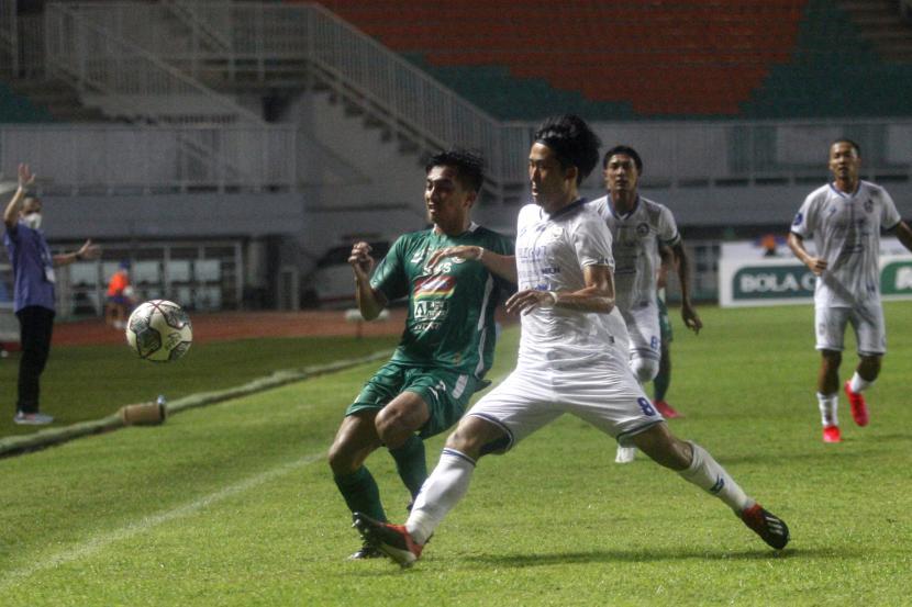 Pesepak bola PSS Sleman Fitra Ridwan (kiri) berebut bola dengan pesepak bola Arema FC Renshi Yamaguchi (kanan) dalam laga lanjutan Liga 1 di Stadion Pakansari, Kabupaten Bogor, Jawa Barat, Ahad (19/9/2021).