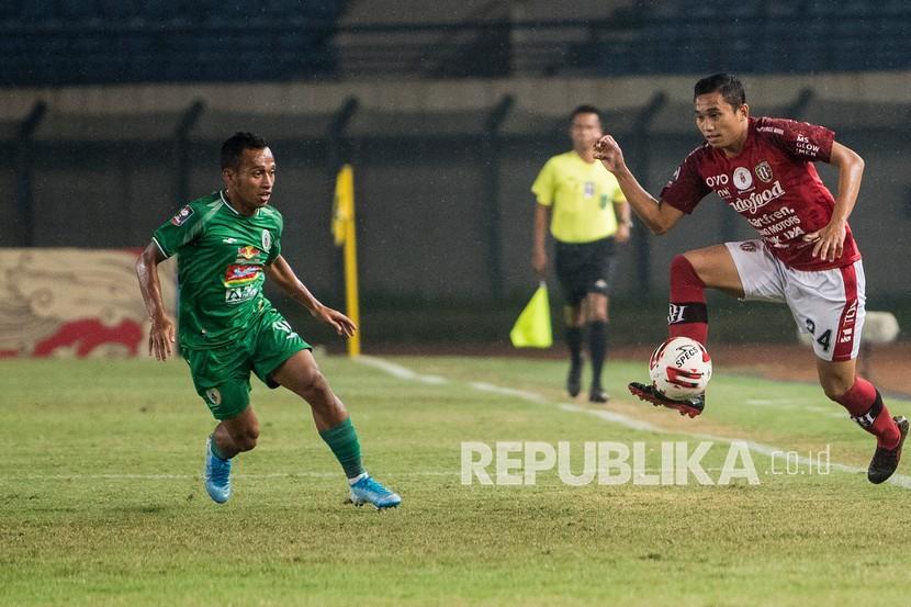 Pesepak bola PSS Sleman Irfan Jaya (kiri) berusaha menghadang laju pesepak bola Ricky Fajrin (kanan) saat pertandingan sepak bola perempat final Piala Menpora 2021 di stadion Si Jalak Harupat, Kabupaten Bandung, Jawa Barat, Senin (12/4/2021).