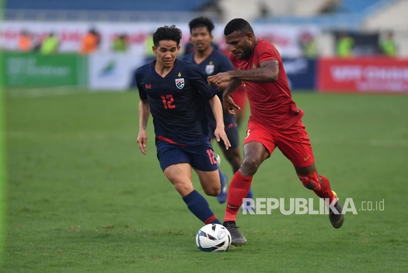 Pesepak bola tim nasional U-23 Indonesia Marinus Manewar (kanan) menggiring bola dibayangi pesepak bola tim nasional Thailand U-23 Thawornsak Kannarin (kiri), pada pertandingan perdana Grup K kualifikasi Piala Asia U-23 AFC 2020, di Stadion Nasional My Dinh, Hanoi, Vietnam, Jumat (22/3/2019).