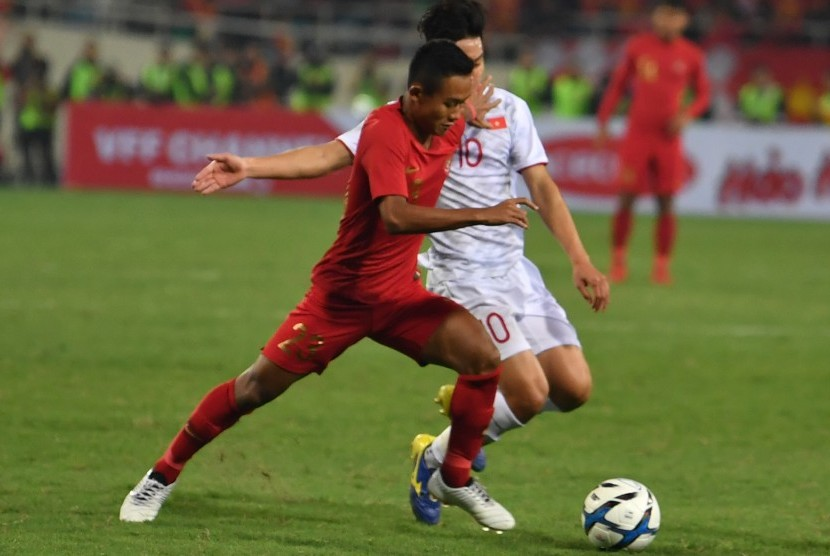 Gelandang timnas Indonesia U-23 Sani Rizki (kiri) berupaya melewati pemain Vietnam U-23 Truong Van Thay Qui pada pertandingan sepak bola Grup K kualifikasi Piala AFC U-23 di Stadion Nasional My Dinh, Hanoi, Vietnam, Ahad (24/3/2019).