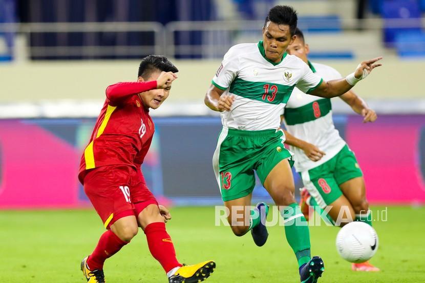 Pesepak bola Timnas Indonesia Rachmat Irianto (kanan) mempertahankan bola dari kawalan pesepak bola Timnas Vietnam Nguyen Quang Hai (kiri) dalam pertandingan Grup G Kualifikasi Piala Dunia 2022 zona Asia di Stadion Al Maktoum, Dubai, Uni Emirat Arab, Senin (7/6/2021) malam. Timnas Indonesia kalah dari Timnas Vietnam dengan skor 0-4 dalam pertandingan tersebut.