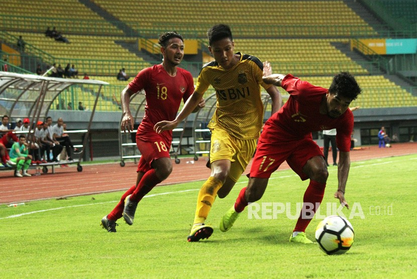 Pesepak bola Timnas Indonesia U-22 R.Lastori (kanan) berebut bola dengan pesepak bola Bhayangkara FC Arif Setiawan (tengah) pada laga pertandingan persahabatan di Stadion Patriot Candrabhaga, Bekasi, Jawa Barat, Rabu (6/2/2019).