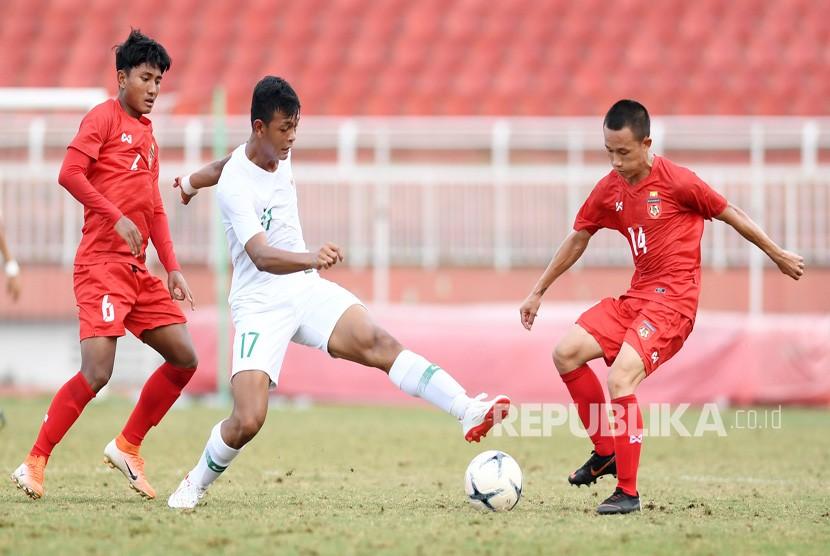 Pesepakbola Indonesia Saddam Emiruddin (tengah) berusaha melewati dua pesepakbola Myanmar Ye Min Kyew (kanan) dan Yan Kyaw Soe, saat bertanding pada penyisihan Grup A Piala AFF U-18 2019 di Stadion Thong Nhat, Ho Chi Minh, Vietnam, Rabu (14/8/2019).