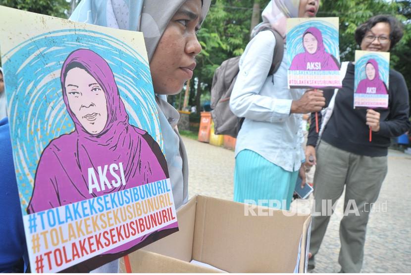 Peserta aksi menunjukkan poster dan kotak donasi pada aksi Tolak Eksekusi Baiq Nuril Maknun di Taman Kamabang Iwak Palembang, Minggu (18/11/2018).