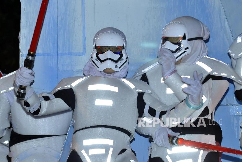 Peserta pawai mengenakan kostum karakter Storm Troopers dari film Starwars pada pawai Bandung Light Fest bertemakan Robot Galactica di Jalan Merdeka, Kota Bandung, Ahad (9/10) malam.