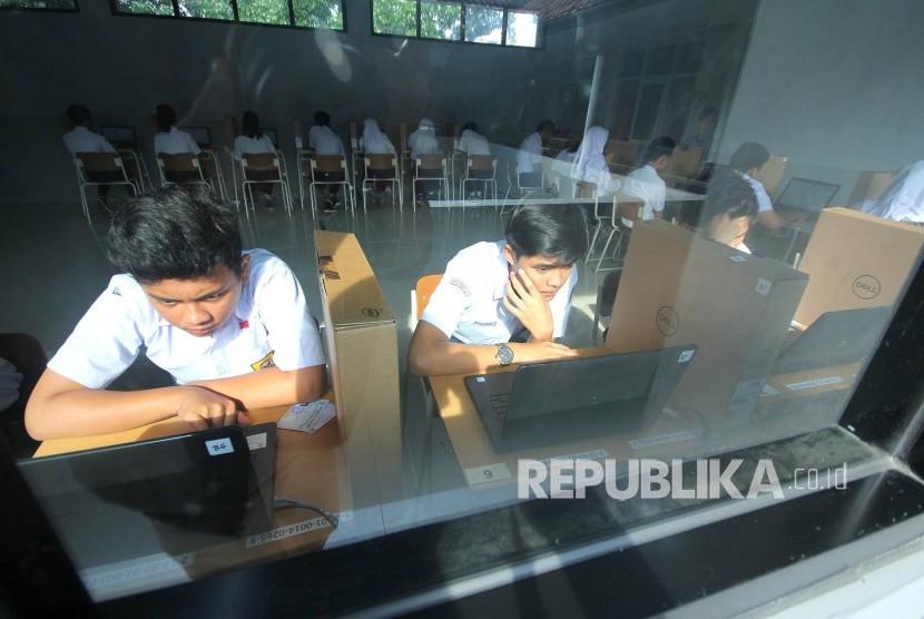 Peserta ujian mengerjakan soal saat Ujian Nasional Berbasis Komputer (UNBK), di SMPN 14 Bandung, Jalan Supratman, Kota Bandung, Senin (22/4).