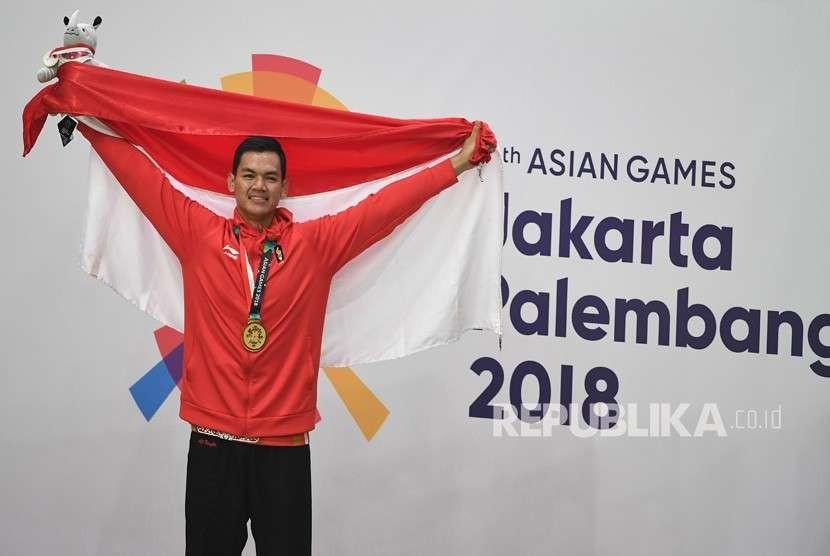Pesilat Indonesia peraih medali emas Aji Bangkit Pamungkas berpose usai upacara penyerahan medali nomor Kelas I Putra Asian Games 2018 di Padepokan Pencak Silat Taman Mini Indonesia Indah (TMII), Jakarta, Senin (27/8).