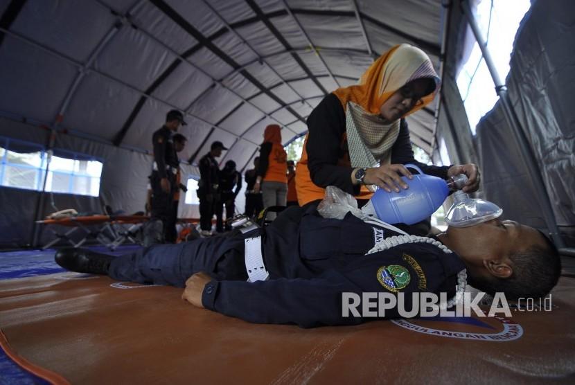 Petugas Badan Nasional Penanggulangan Bencana (BNPB) melakukan evakuasi korban bencana saat glasi bersih simulasi penanganan bencana gempa di Halaman Gedung Sate, Jalan Diponegoro, Kota Bandung, Senin (24/4).
