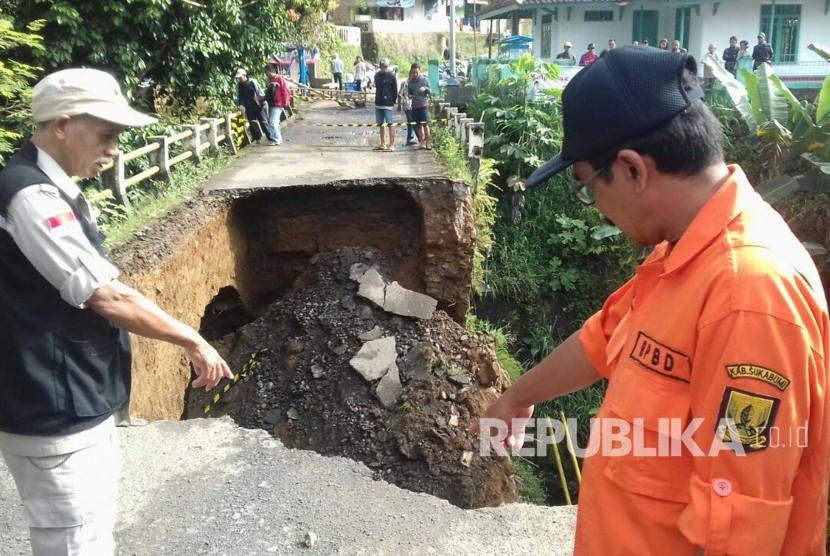 Petugas Badan Penanggulangan Bencana Daerah (BPBD) Kabupaten Sukabumi meninjau jembatan yang ambruk di perbatasan antara Kecamatan Parungkuda dan Ciambar, Kabupaten Sukabumi, Selasa (24/1).