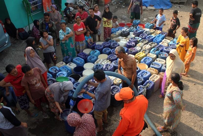Petugas Badan Penanggulangan Bencana Daerah (BPBD) memberikan bantuan air bersih kepada warga yang dilanda kekeringan.