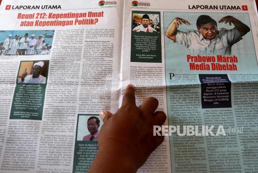 Petugas Badan Pengawas Pemilu (Bawaslu) Kabupaten Banyuwangi menunjukkan isi Tabloid Indonesia Barokah di Glagah, Banyuwangi, Jawa Timur, Jumat (25/1/2019).