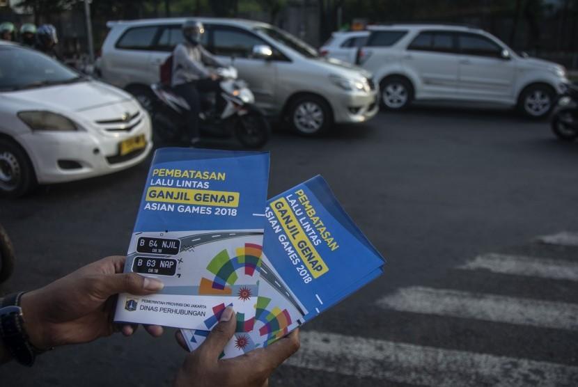 Petugas Badan Pengelola Transportasi Jabodetabek (BPTJ) melakukan sosialisasi kepada pengguna kendaraan bermotor pada hari pertama uji coba perluasan kawasan ganjil genap di persimpangan Pancoran, Jakarta, Senin (2/7).