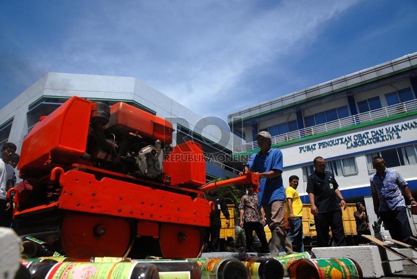 Petugas Balai Pengawas Obat dan Makanan (BPOM) memusnahkan barang bukti obat dan makanan ilegal secara simbolik di lapangan kantor BPOM, Jakarta Timur, Selasa (19/11).  (Republika/Rakhmawaty La'lang)