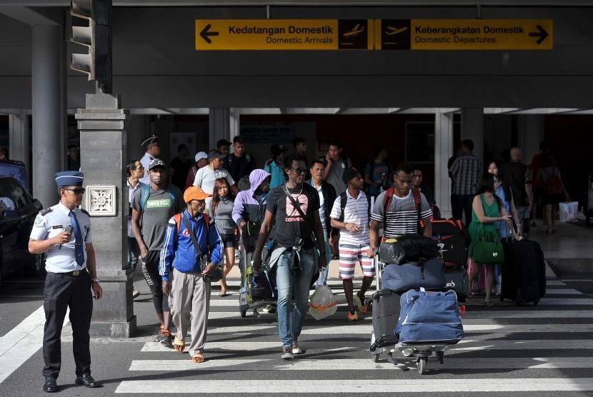 Petugas bandara mengawasi penumpang yang baru tiba di terminal kedatangan domestik Bandara Ngurah Rai, Denpasar, Jumat (24/6).