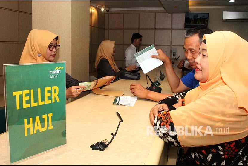Petugas Bank Mandiri Syariah melayani calon jemaah haji melakukan pelunasan Biaya Penyelenggaran Ibadah Haji (BPIH) di Kantor Cabang BSM di Bekasi, Jawa Barat, Senin (16/4). BSM mulai melayani calon jemaah haji yang melakukan pelunasan BPIH pada 16 April hingga 4 Mei 2018