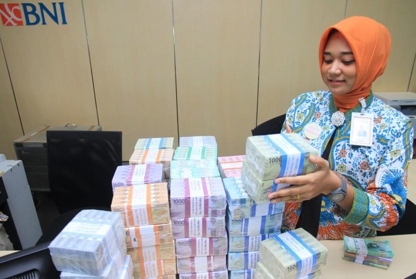 Petugas Bank Negara Indonesia (BNI) Cabang Meulaboh menyiapkan uang pecahan untuk layanan penukaran uang baru di Meulaboh, Aceh Barat, Aceh, Kamis (16/5/2019).