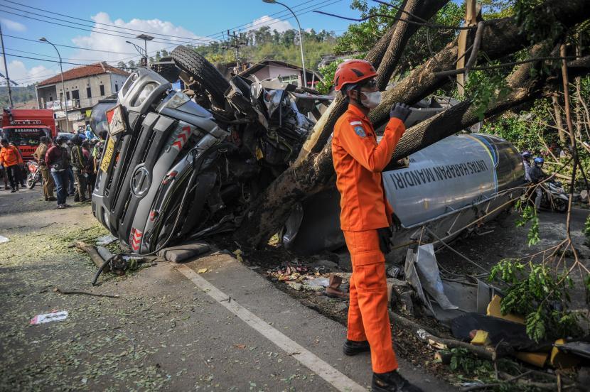 Petugas Basarnas berada di samping truk yang mengalami kecelakaan tunggal di Nagreg, Kabupaten Bandung, Jawa Barat, Selasa (28/9/2021). Kecelakaan truk bermuatan semen cair tersebut diduga karena gagalnya fungsi pengereman hingga mengakibatkan dua orang meninggal.