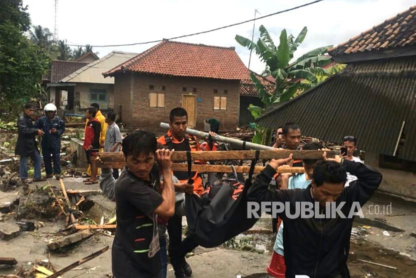 Petugas Basarnas dibantu warga mengevakuasi korban meninggal akibat tsunami di pesisir Cinangka, Serang, Banten, Ahad (23/12).