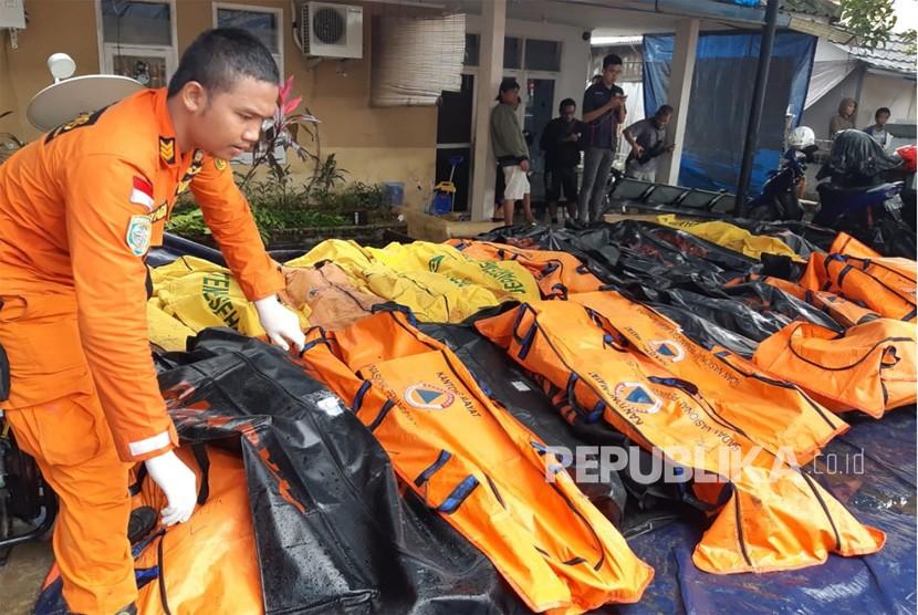 Petugas Basarnas mengumpulkan jenazah korban tsunami di pesisir Cinangka, Serang, Banten, Ahad (23/12).