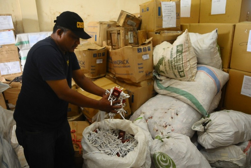 Petugas Bea Cukai menunjukkan barang bukti rokok Sigaret Kretek Mesin (SKM) ilegal di kantor Bea dan Cukai Kudus, Jawa Tengah, Selasa (15/1/2019).