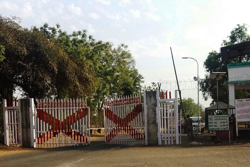Petugas berdiri di gerbang Kakrapar Atomic Power Station di Gujarat pada 11 Maret 2016. Reaktor nuklir India dimatikan setelah mengalami kebocoran.