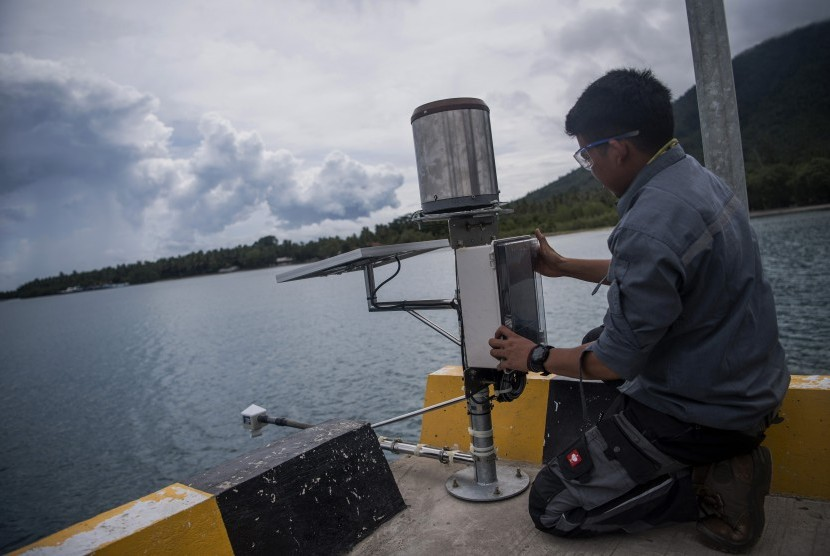 Petugas BMKG memasang alat pengukur ketinggian air atau