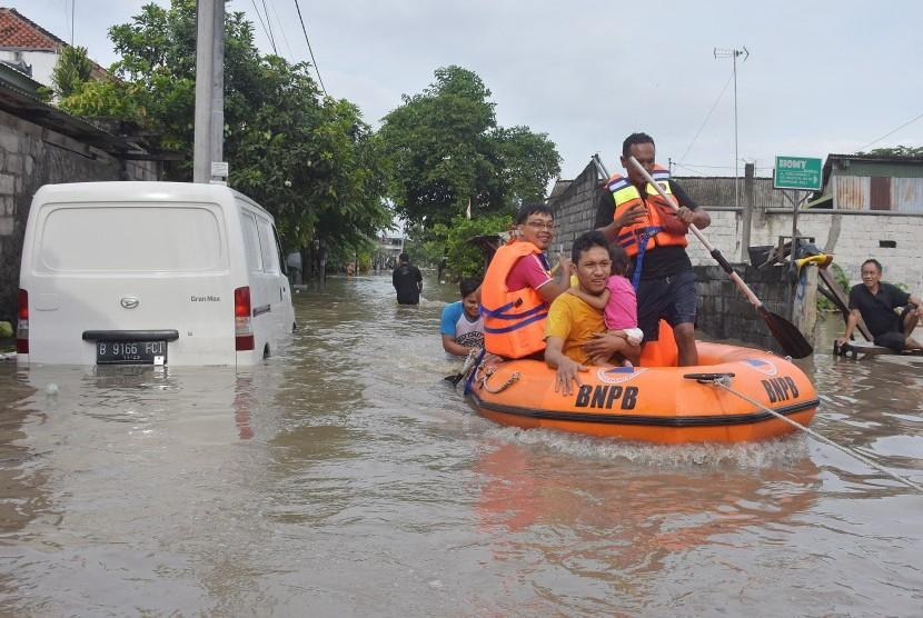 Petugas BNPB mengevakuasi warga akibat banjir di kawasan perumahan jalan Pura Demak, Denpasar, Sabtu (8/12/2018).