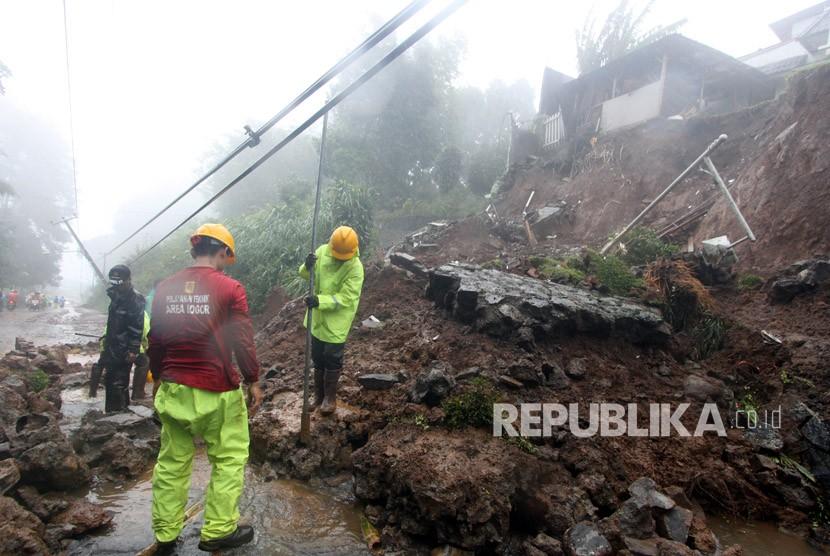 Petugas BPBD Kabupaten Bogor berusaha membersihkan material longsor yang menutupi jalur utama Puncak Bogor, Jawa Barat, Senin (5/2).