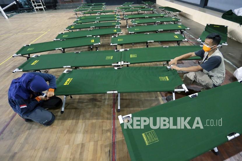 Petugas BPBD merakit tempat tidur darurat di Rumah Sakit Lapangan (RSL) GOR Soekarno-Hatta Kota Blitar, Jawa Timur, Jumat (30/7/2021). Pemkot Blitar mengubah GOR Indoor Soekarno-Hatta menjadi rumah sakit darurat untuk pasien COVID-19 bergejala sedang hingga ringan dengan daya tampung sekitar 60 tempat tidur pasien.