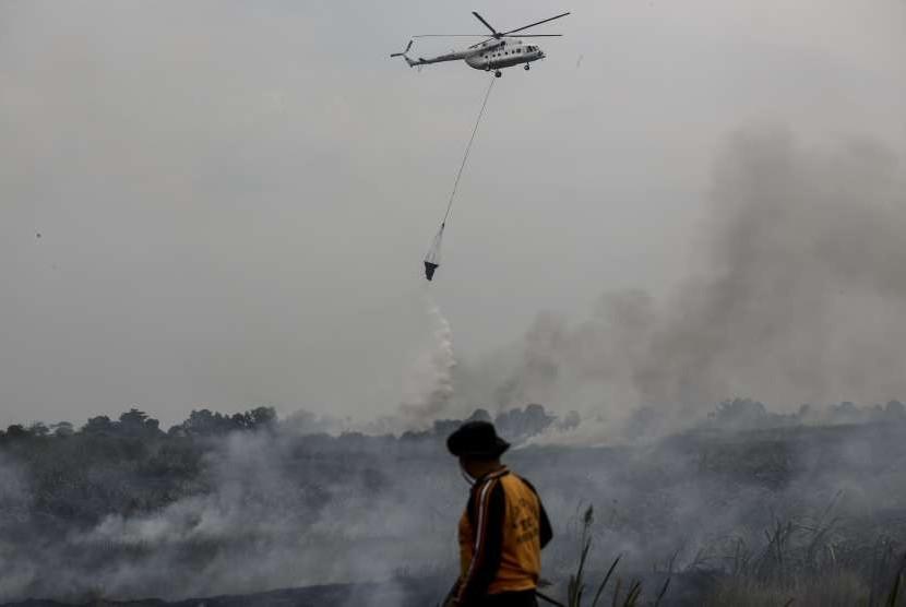 Petugas BPBD Provinsi Sumatera Selatan dibantu Helikopter MI-8Mtv milik Badan Nasional Penanggulangan Bencana (BNPB) melakukan pemadaman kebakaran lahan di Desa Rambutan, Banyuasin, Sumatra Selatan, Minggu (16/9).