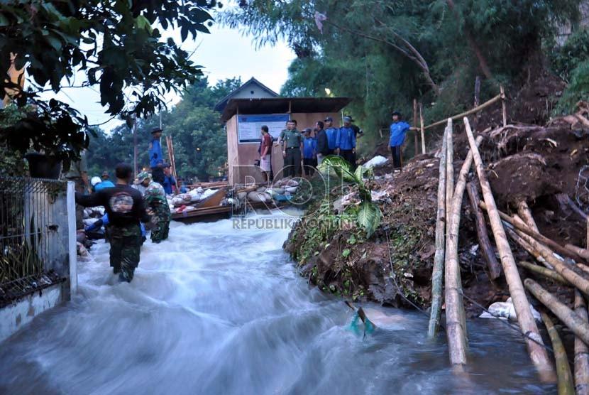 Petugas dan anggota Satgas Banjir Dinas Bina Marga dan Sumber Daya Air Depok masih kesulitan menutup tanggul Kali Laya yang jebol dini hari tadi di kawasan Cimanggis, Depok, Selasa (13/11). (Rakhmawaty La'lang)