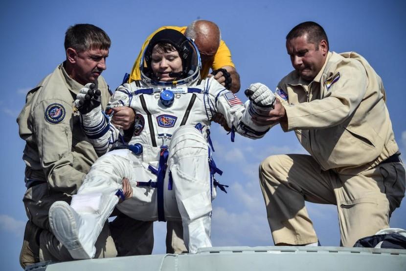 Petugas darat membantu astronot Anne McClain (tengah).