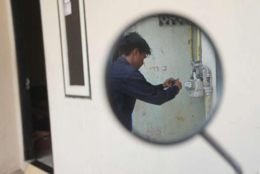 Petugas dari Perusahaan Gas Negara (PGN) melakukan pencatatan meter (cater) mengunakan kamera digital.