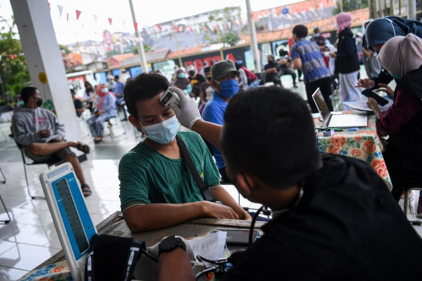 Petugas dari Puskesmas Kecamatan Cilandak memeriksa suhu warga sebelum divaksin COVID-19 di RPTRA Bahari, Gandari Selatan, Jakarta Selatan, Kamis (6/5/2021). Pemprov DKI Jakarta mulai melakukan vaksinasi bagi warga usia 18 tahun ke atas yang berada di RW rentan dan padat penduduk.