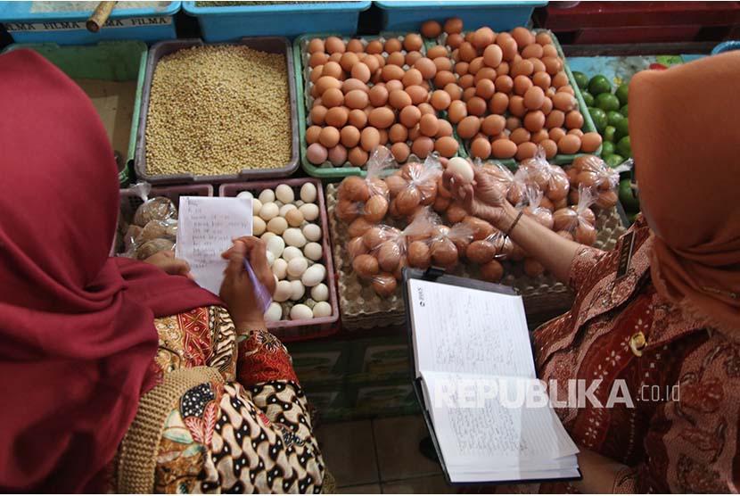 Petugas dari Tim Pengendali Inflasi Daerah (TPID) melakukan inspeksi mendadak ketersediaan telur ayam di pasar Pahing, Kota Kediri, Jawa Timur, Selasa (10/7). Sepekan terakhir harga telur ayam terus mengalami kenaikan dari sebelumnya Rp21.000 menjadi Rp26.000 per kilogram karena pasokan telur menurun hingga 30 persen akibat cuaca buruk.